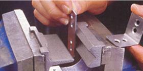 """Étau d'établis et accessoires - L'étau de menuisier est muni de mors en bois pour ne pas endommager le fini du matériau maintenu. L'étau de mécanicien est en acier.  Ses mors peuvent recevoir un accessoire avec lequel on peut plier des minces plaques d'acier à 90 degrés. L'établi de travail du métal est muni d'une petite plaquette """"wire-bender"""" permettant de tordre des petites tiges de métal."""